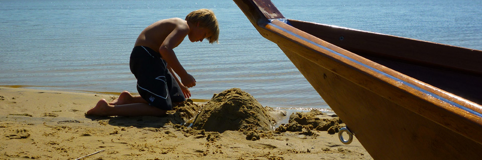 kid on the beach with nice woodenboat au lacanau lake france